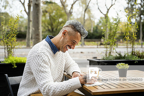 Happy man writing in book while taking tea break in cafe
