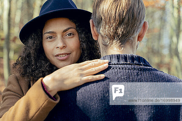 Woman wearing hat hugging man while standing in forest