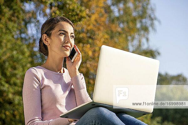 Junge Unternehmerin  die mit ihrem Laptop im Herbst im Park sitzt und mit ihrem Smartphone telefoniert Junge Unternehmerin, die mit ihrem Laptop im Herbst im Park sitzt und mit ihrem Smartphone telefoniert