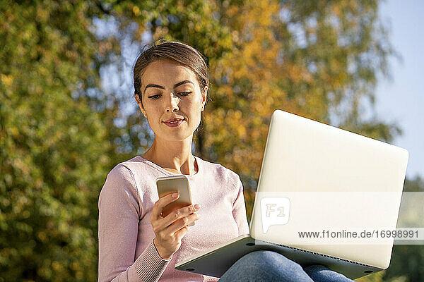 Geschäftsfrau  die im Herbst im Park sitzt und mit ihrem Smartphone SMS schreibt Geschäftsfrau, die im Herbst im Park sitzt und mit ihrem Smartphone SMS schreibt
