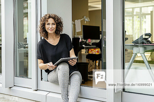 Smiling businesswoman using digital tablet while sitting at office door