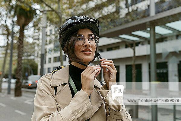 Frau mit Fahrradhelm auf der Straße in der Stadt Frau mit Fahrradhelm auf der Straße in der Stadt