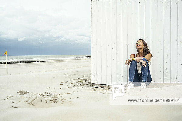 Woman relaxing while sitting with eyes closed at beach