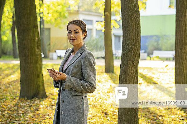 Female entrepreneur holding smart phone in park during autumn season