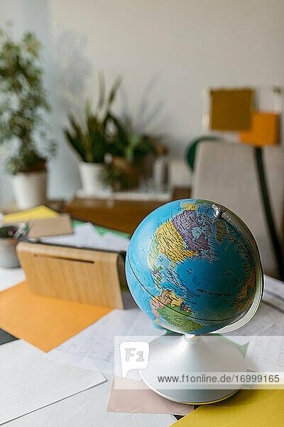 Weltkugel mit Papieren auf dem Tisch Weltkugel mit Papieren auf dem Tisch