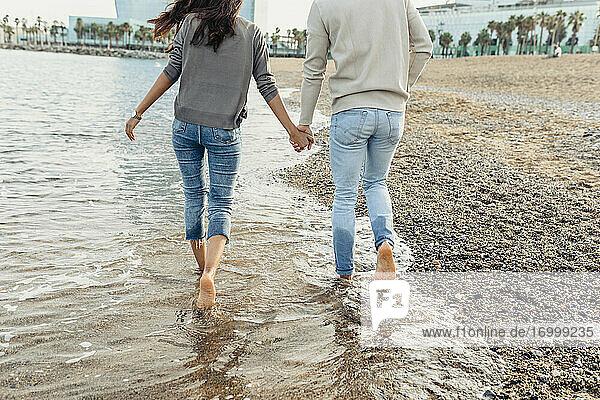 Junges Paar hält sich an den Händen  während es am Strand über das Wasser läuft Junges Paar hält sich an den Händen, während es am Strand über das Wasser läuft