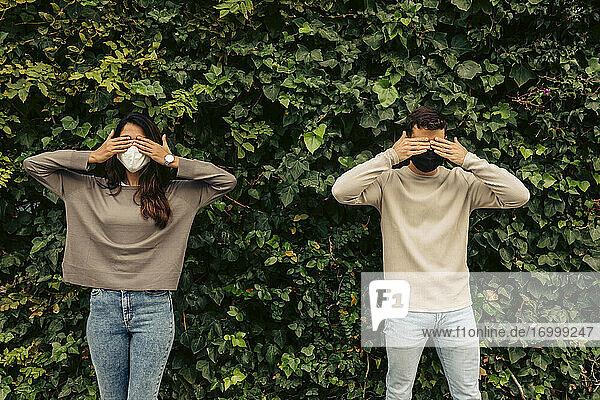 Junges Paar  das seine Augen mit den Händen vor Pflanzen im Park abdeckt  während COVID-19 Junges Paar, das seine Augen mit den Händen vor Pflanzen im Park abdeckt, während COVID-19