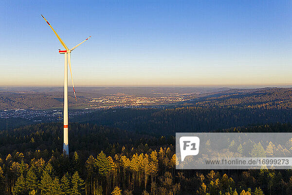 Wind turbine standing in autumn forest at dusk