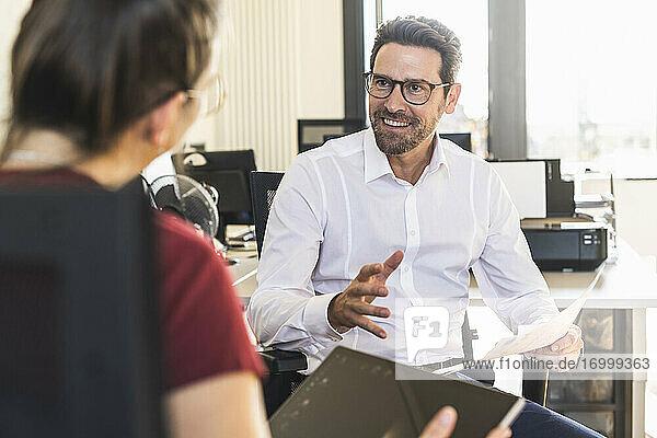 Lächelnder Geschäftsmann plant mit einem Kollegen  der ein digitales Tablet benutzt  im Büro