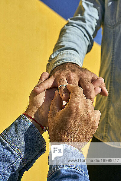 Gay man putting ring in young man finger while standing by yellow wall