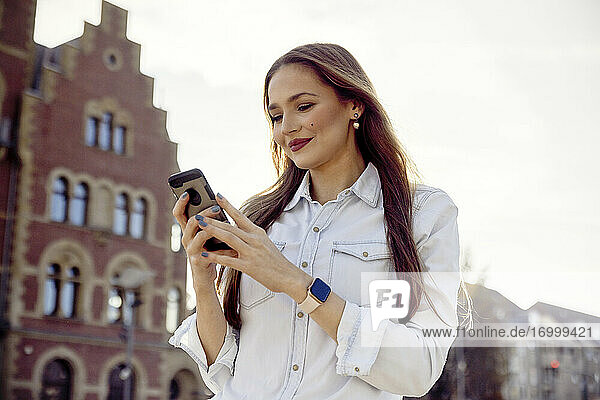Smiling businesswoman using mobile phone while standing against sky