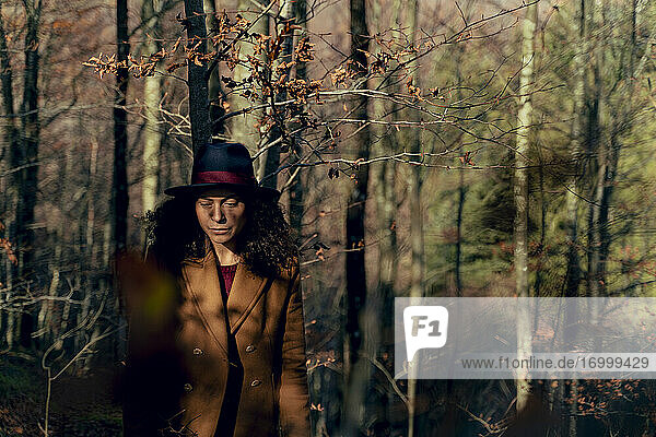 Sad woman looking down while standing in forest