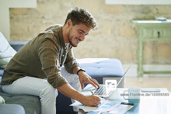 Lächelnder Geschäftsmann  der am Laptop im Wohnzimmer sitzt und auf Papier schreibt Lächelnder Geschäftsmann, der am Laptop im Wohnzimmer sitzt und auf Papier schreibt