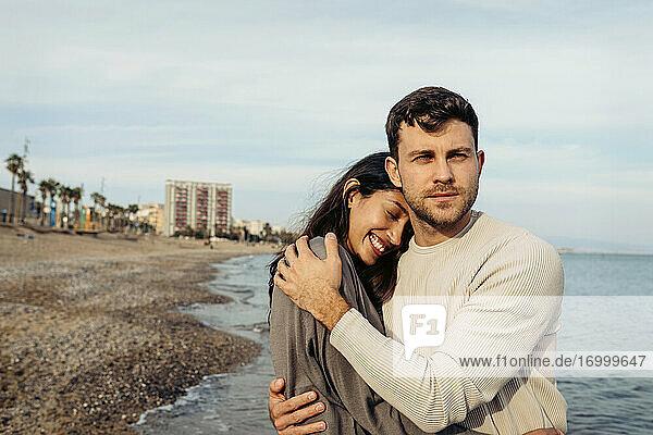 Lächelndes junges Paar umarmt sich am Strand Lächelndes junges Paar umarmt sich am Strand