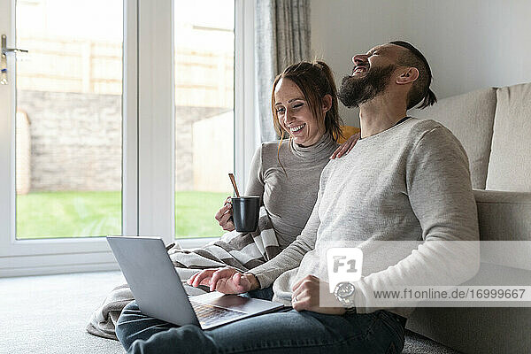 Man laughing while watching movie on laptop with girlfriend at home