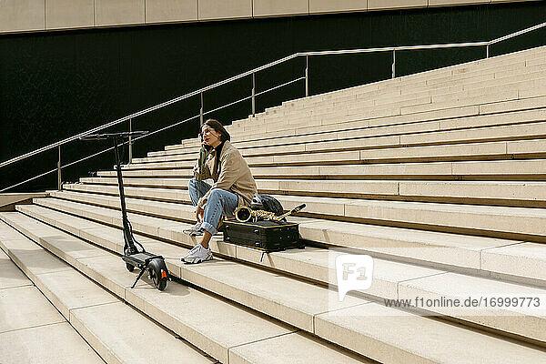 Frau  die mit einem Mobiltelefon spricht  während sie neben einem Saxophoninstrument und einem elektrischen Roller auf einer Treppe sitzt Frau, die mit einem Mobiltelefon spricht, während sie neben einem Saxophoninstrument und einem elektrischen Roller auf einer Treppe sitzt