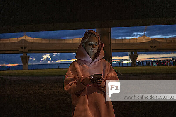 Young woman with pink hair wearing pink hooded shirt holding smart phone in city at night