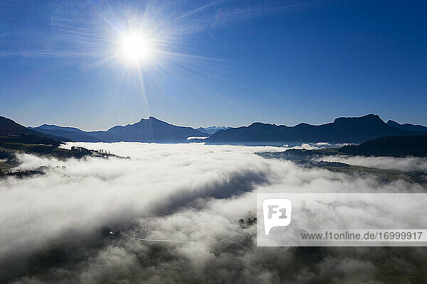 Drone view of Drachenwand and Schafberg mountains protruding from sea of thick fog