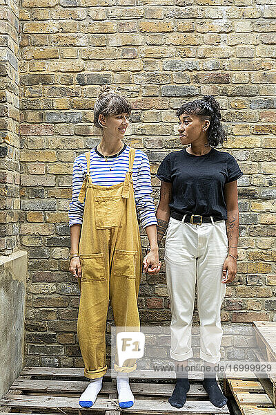 Young lesbian couple smiling while standing on bench against brick wall