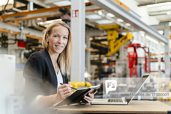 Smiling businesswoman holding diary while sitting with laptop in industry