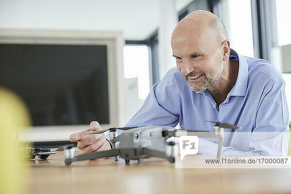 Businessman checking quadcopter at home