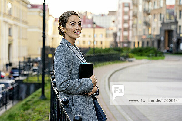 Thoughtful businesswoman leaning on railing in city during autumn