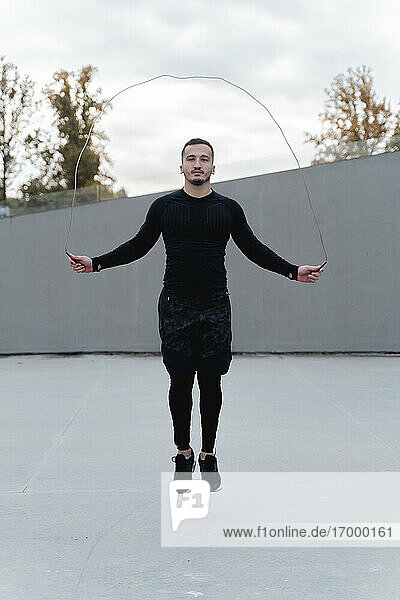 Young man skipping rope while exercising outdoors