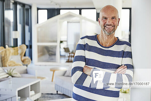 Smiling man standing with arms crossed at home