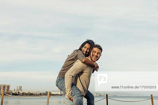 Glücklicher Freund  der seine Freundin huckepack nimmt  steht am Meer vor dem Himmel Glücklicher Freund, der seine Freundin huckepack nimmt, steht am Meer vor dem Himmel