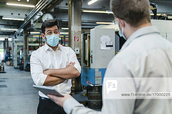 Businessman looking at male coworker while discussing in factory during COVID-19