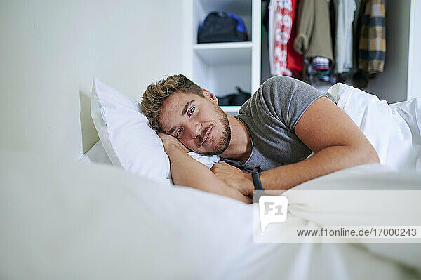 Smiling man lying on bed in bedroom at home