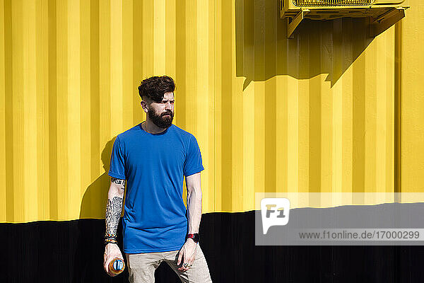 Young man with tattoo standing in front of yellow wall  holding water bottle