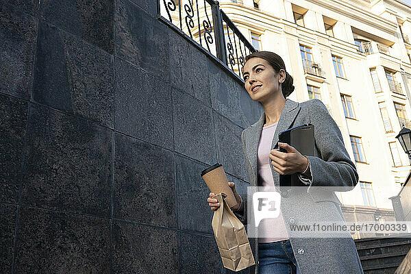 Lächelnde junge Geschäftsfrau  die eine Treppe in der Stadt hinuntergeht Lächelnde junge Geschäftsfrau, die eine Treppe in der Stadt hinuntergeht