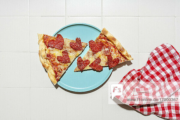 Pizza with pepperoni in heart shapes on blue plate  white tiles and white and red checkered napkin