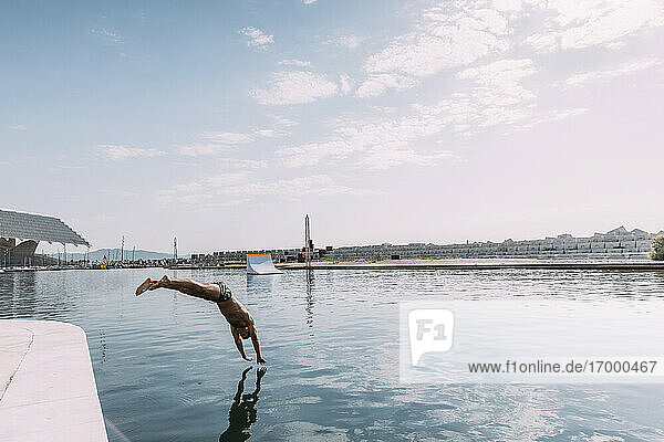 Young man jumping into water from a pier