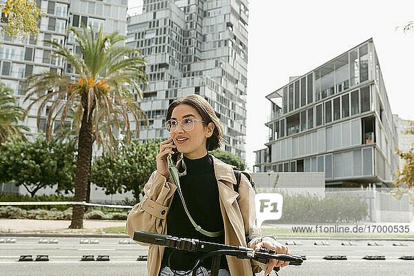 Lächelnde Frau  die mit einem Mobiltelefon spricht  während sie mit einem Elektroroller in der Stadt steht Lächelnde Frau, die mit einem Mobiltelefon spricht, während sie mit einem Elektroroller in der Stadt steht