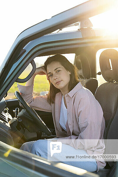 Young woman sitting in car during road trip
