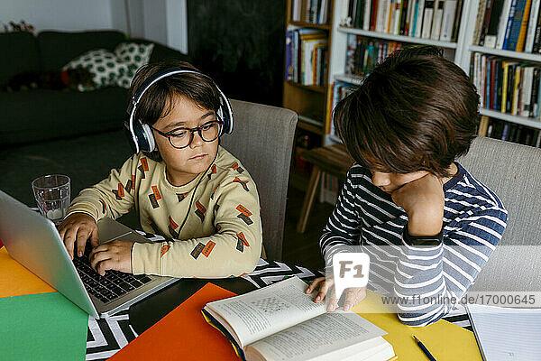 Junge guckt  während sein Freund am Tisch ein Lehrbuch liest Junge guckt, während sein Freund am Tisch ein Lehrbuch liest