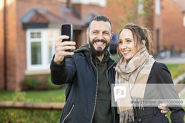 Smiling man taking selfie with girlfriend while standing outside new house