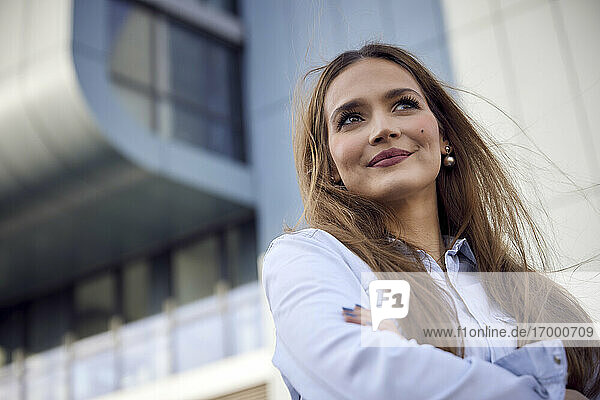 Thoughtful businesswoman looking away while standing outdoors