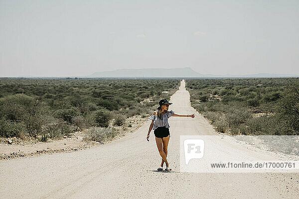 Namibia  woman hitchhiking on the road to Spitzkoppe