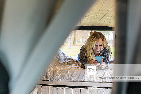 Comfortable woman lying on bed while using mobile phone in camper van