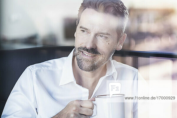 Smiling businessman drinking coffee while sitting at office