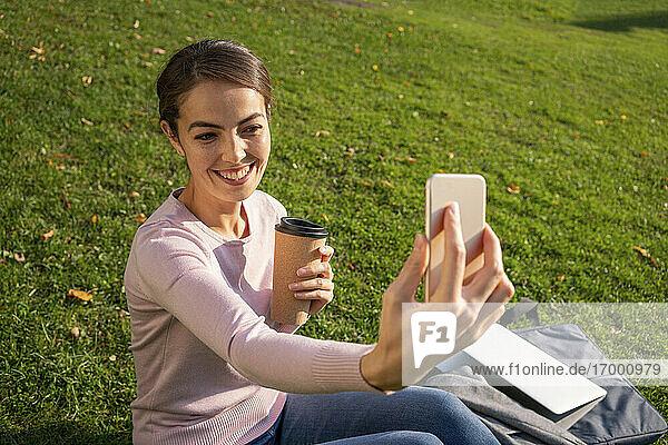 Glückliche Geschäftsfrau  die ein Selfie mit ihrem Smartphone macht  während sie im Herbst auf einer Wiese im Park sitzt Glückliche Geschäftsfrau, die ein Selfie mit ihrem Smartphone macht, während sie im Herbst auf einer Wiese im Park sitzt