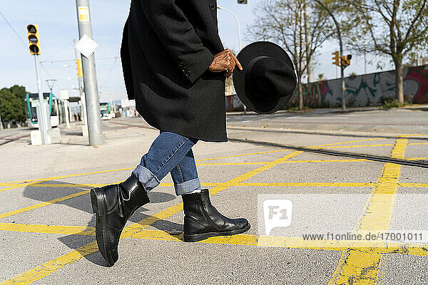 Fashionable man holding hat while walking on street