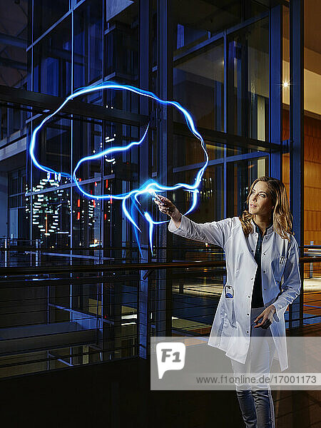 Female doctor light painting brain at laboratory in hospital