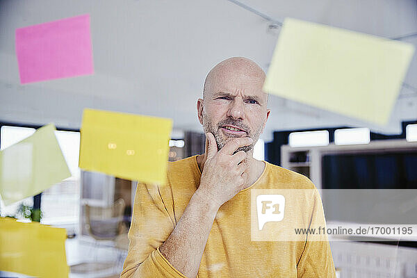 Confused man with hand on chin reading adhesive note