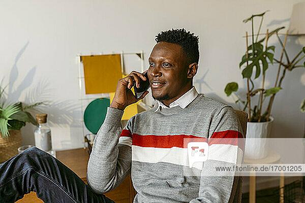 Lächelnder Geschäftsmann  der mit seinem Smartphone telefoniert  während er zu Hause sitzt Lächelnder Geschäftsmann, der mit seinem Smartphone telefoniert, während er zu Hause sitzt
