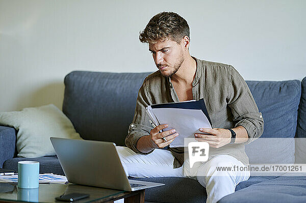 Businessman working on laptop while holding paper in living room
