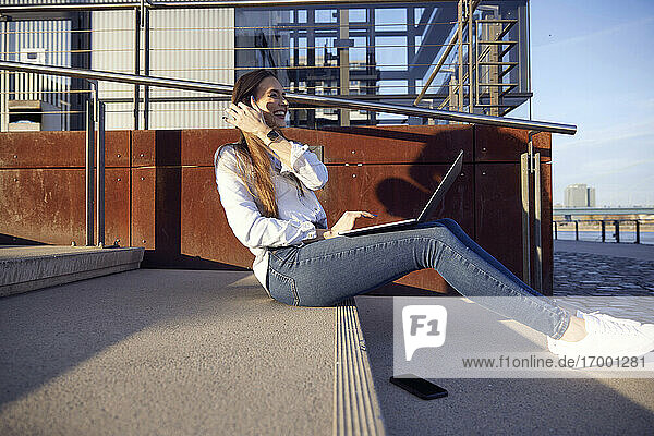 Happy businesswoman working on laptop while sitting on steps during sunset